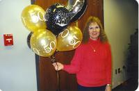 "Minnesota State University, Mankato, library staff member Rosie Mock celebrating her 50th birthday: holding ""Over the Hill"" balloons. March 9, 1999"