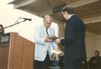 Mankato State University, President Dr. Richard Rush giving out awards during the commencement ceremony, June 1989