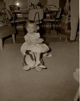 Girl sitting on a stuffed animal at Mankato State College, 1958-05-06.