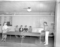 Two students playing ping pong while four students watch at Mankato State College, 1958-03-31.