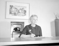 Marie Bruce, Dean of Women, sitting at a desk writing on paper at Mankato State College, 1958-03-31.