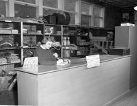 Jean Garvin sitting at the equipment desk at Mankato State College, 1958-03-31.