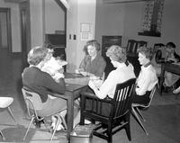 Five women playing cards in a student lounge at Mankato State College, 1958-03-31.