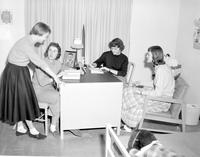 Four women sitting at a desk in a dormitory room at Mankato State College, 1958-03-31.
