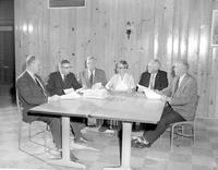 Six Mankato State College faculty members sitting around a table while looking at papers, 1958-03-25.