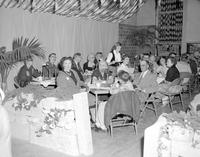 A group of people sitting at tables a a party at Mankato State College, 1958-03-31.