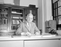Nelson, Maurice J. Professor of Sociology sitting at a desk at Mankato State College, 1958-03-31.