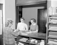 A woman helps two other women at the library at Mankato State College 03-31-1958.