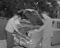 Mankato State College, three individuals checking out the engine of a Mankato State service car, June 4, 1958