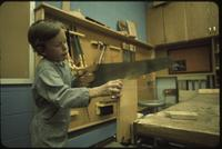 Mankato State College, child with hammer in a work shop class, 1975-06.