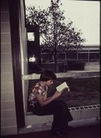 Mankato State University, girl with book sitting in Wiecking near the plaza, June 1977