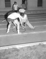 College students pushing a shot put ball around a ring at Mankato State College 1959-06-17