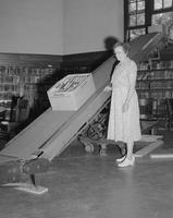 Female watching conveyor belt as new books come in at Mankato State College, 1959-09-22.