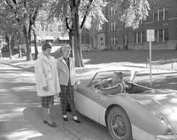 Rosalie Abraham and Marge Kropp conversing with Jim Hamann in Austin Healy at Mankato State College, 1959-10-05.