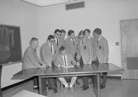 Service fraternity Beta Delta Tau members at a table at Mankato State College 1964-02-13