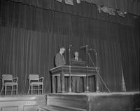 Two men standing on stage, Mankato State College, 1964-02-14.