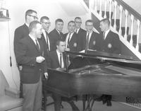 Alpha Beta Mu members singing by piano at Mankato State College 1964-03-02