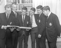 Members of the Alpha Beta Mu fraternity looking at a book 1964-03-02
