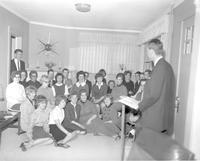 Man standing in front of a group of seated men and women, at Mankato State College 1964-03-08