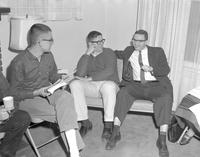 Seated men at a script reading, at Mankato State College 1964-03-06