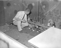 Man picking stones from broken pieces of liquor bottles at Mankato State College,1964-04-19.