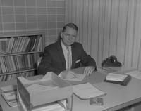 Andrew R. Een, principal of Wilson Campus School sitting at his desk, Mankato State College, 1962-01-22.