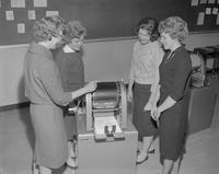 Teacher and students surrounding a duplicating machine at Mankato State College, 1962-01-22.