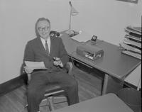 Man siting in his office holding a piece of paper and a Dictaphone at Mankato State College, 1962-01-22.