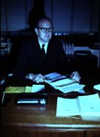 Dr. Nickerson sitting at his desk at Mankato State College, 1968-06-20.