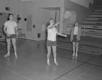 Three students play badminton, Mankato State College, 1962-01-22.