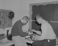 Two men work on a radio, Mankato State College, 1962-01-26.