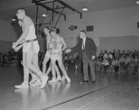 A man talking to five male basketball players before their game at Mankato State College, 1962-01-22.