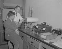 John McCarty helping student check equipment at Mankato State College, 1962-02-05.