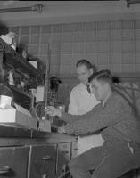 John McCarty helping student with experiment at Mankato State College, 1962-02-05.