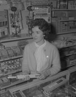 A female sales clerk at Mankato State College, 1962-02-09.