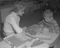 Teacher sitting with child building a toy at Mankato State College, 1962-03-23.