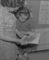 Little girl showing teacher an art project at Mankato State College, 1962-03-23.