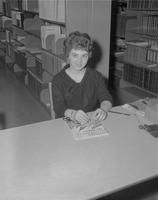 "Shot of Norma Dick sitting at library circulation desk for ""Who's Who"" at Mankato State College, 1962-03-28."