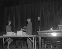 President C.L. Crawford awarding diplomas at fall commencement at Mankato State College, 1962-12-06.