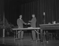 President Crawford awarding diplomas at fall commencement at Mankato State College,1962-12-06.