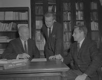 Three men in suits having a deep conversation at Mankato State College, 1962-11-26.