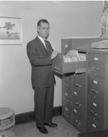 M.A. Freeman posed by file cabinet at Mankato State College, 1962-12-11.