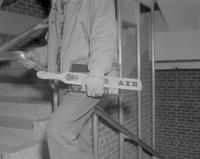 Student walking around with fraternity hazing paddle at Mankato State College, 1962-12-18.