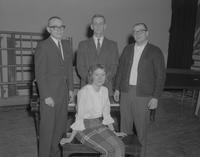 Three men standing and a woman sitting on a piano bench, Mankato State College, 1962-03-13.