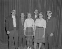 Four men and two women standing in front of a curtain, Mankato State College, 1962-03-13.