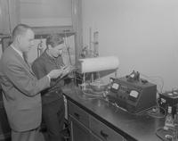 Student with instructor working on a machine at Mankato State College, 1962-01-07.