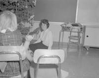 Two women doing decorations while talking at Mankato State College, 1962-01-07.