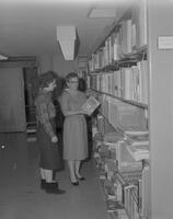 Two women looking at a book in the Library at Mankato State College, 1962-01-07.