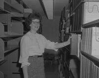 Women pulling books at the Library at Mankato State College, 1962-01-07.
