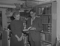 A man and Woman looking at a book in the Library at Mankato State College, 1962-01-07.
